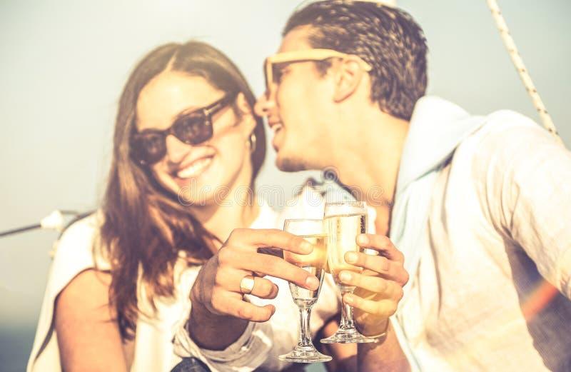 Pares jovenes de los amantes en el velero con el foco en la alegría del vidrio de flauta de champán - concepto alternativo exclus imágenes de archivo libres de regalías