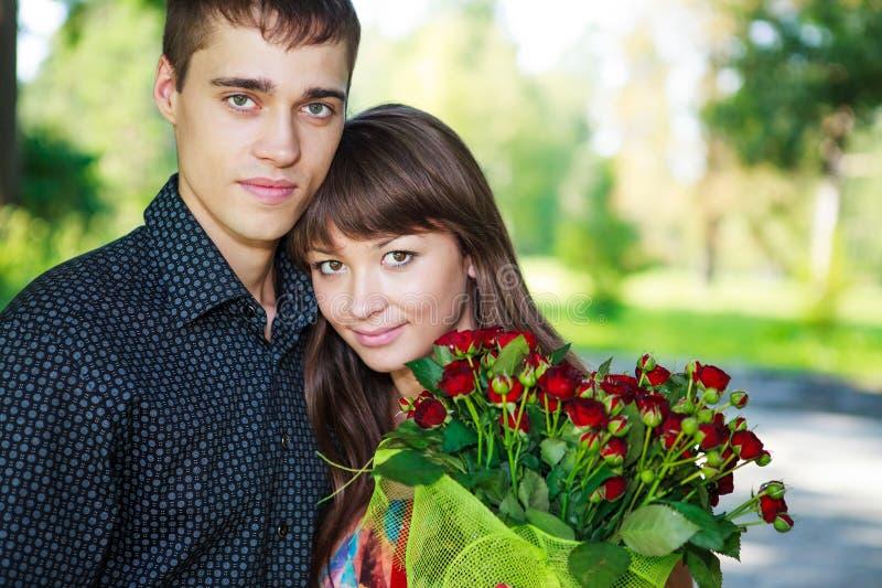 Pares jovenes de los amantes hermosos del retrato con un ramo de ROS rojo imagen de archivo libre de regalías