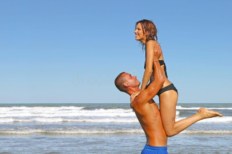 Pares jovenes de los amantes que se divierten en el mar en un día de fiesta de la playa foto de archivo