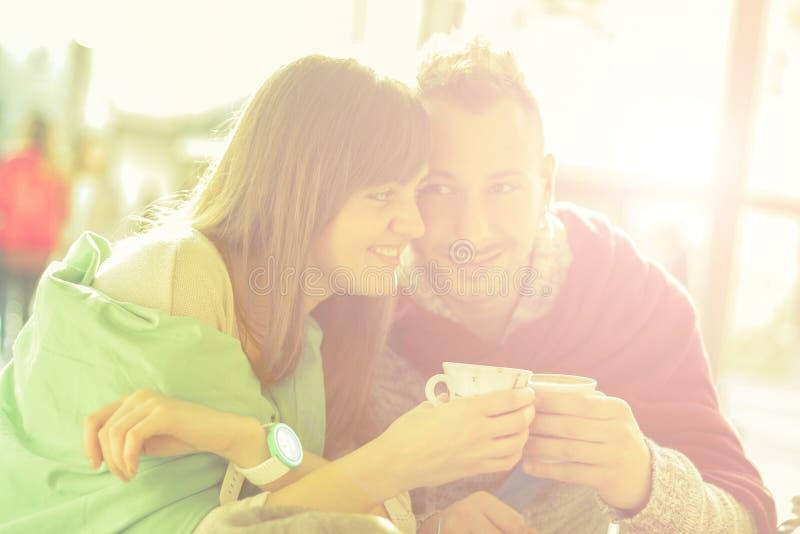 Pares jovenes de los amigos que beben el café en un café foto de archivo libre de regalías