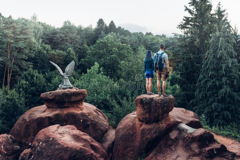 Pares jovenes de los Backpackers que se colocan encima de la montaña y que disfrutan de la vista de la naturaleza en verano imagenes de archivo