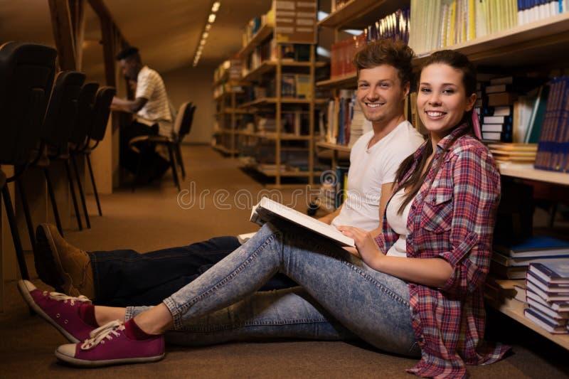 Pares jovenes de los estudiantes alegres que se sientan en el piso y que estudian en la biblioteca de universidad imagenes de archivo