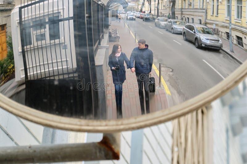 Pares jovenes de los turistas que caminan alrededor de la ciudad con la maleta de la cámara Foco en espejo específico de la calle fotos de archivo libres de regalías