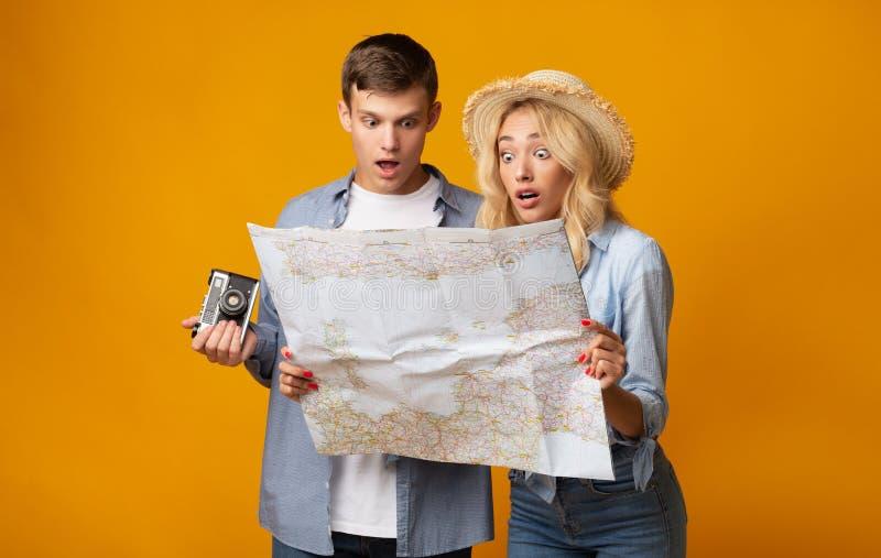 Pares jovenes de los turistas que sostienen un mapa que es chocado imagen de archivo