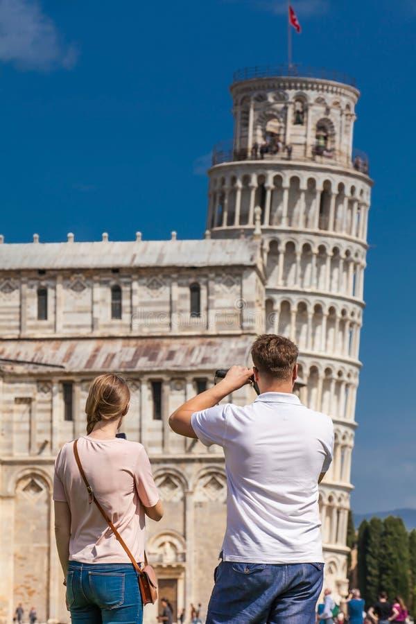 Pares jovenes de los turistas que toman imágenes de la torre inclinada famosa de Pisa fotos de archivo libres de regalías