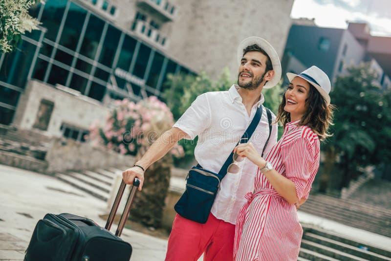 Pares jovenes de los viajeros que buscan el hotel imagenes de archivo