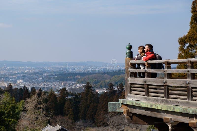 Pares jovenes de los viajeros que miran la ciudad y el paisaje mientras que t foto de archivo