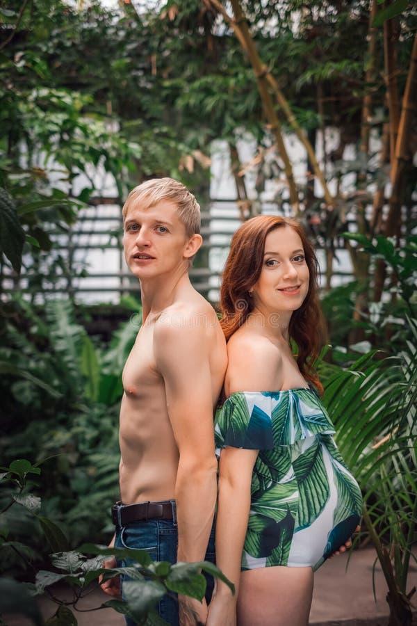 Pares jovenes de pronto a ser padres en el bosque tropical fotos de archivo libres de regalías
