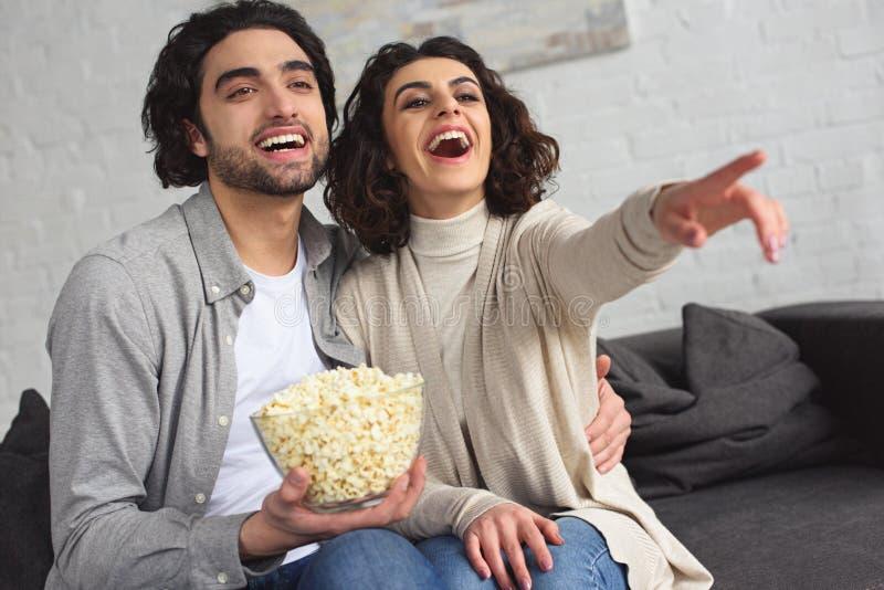 pares jovenes de risa que sostienen el cuenco con palomitas y que miran comedia imágenes de archivo libres de regalías