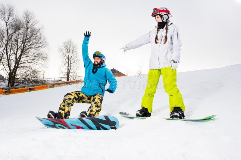 Pares jovenes de snowboarders imagenes de archivo