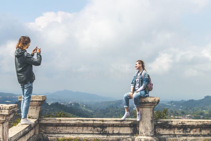 Pares jovenes de turistas en hotel abandonado en el norte de la isla de Bali, Indonesia Hombre que hace la foto de su novia foto de archivo libre de regalías