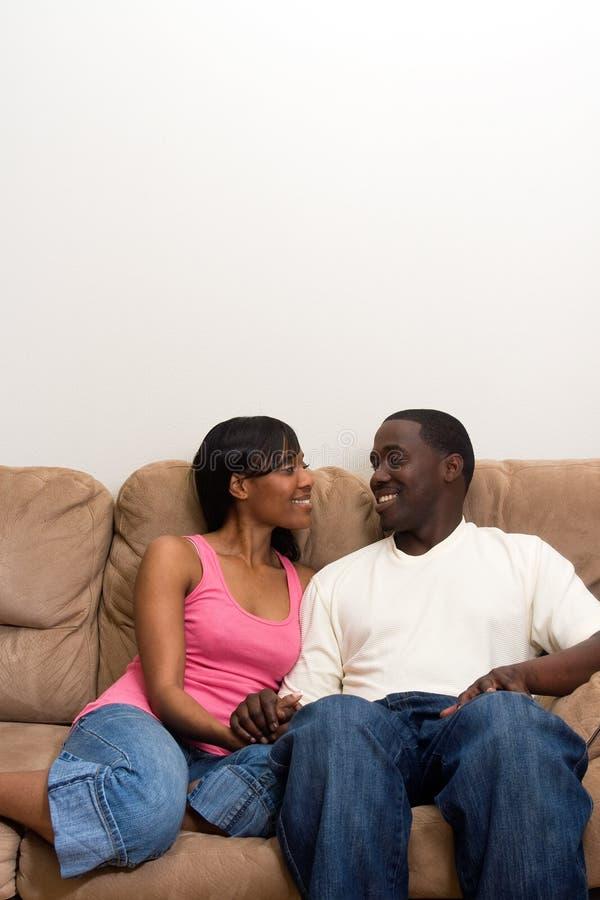 Pares jovenes del afroamericano en su sala de estar fotos de archivo