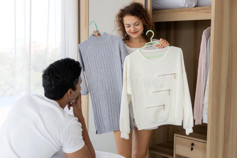 Pares jovenes del amante que eligen la ropa junta en sala de estar en casa imagen de archivo libre de regalías