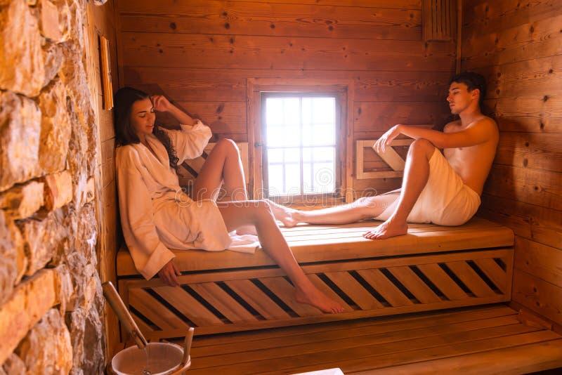 Pares jovenes del amor que se relajan en sauna fotos de archivo