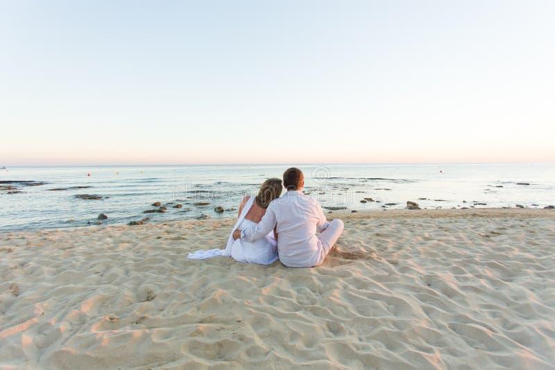 Pares jovenes del amor que se sientan junto en la playa, vista posterior fotos de archivo