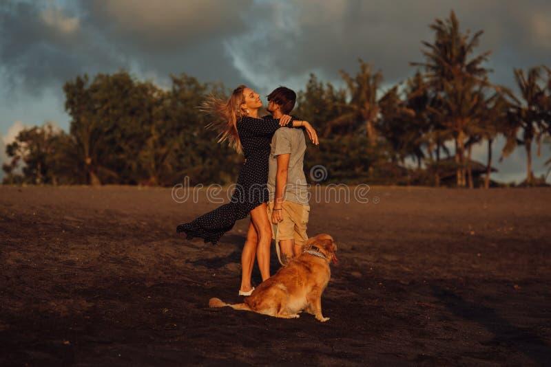Pares jovenes del inconformista de la risa feliz hermosa con golden retriever en la playa océano una arena Ondas concepte de la l foto de archivo libre de regalías
