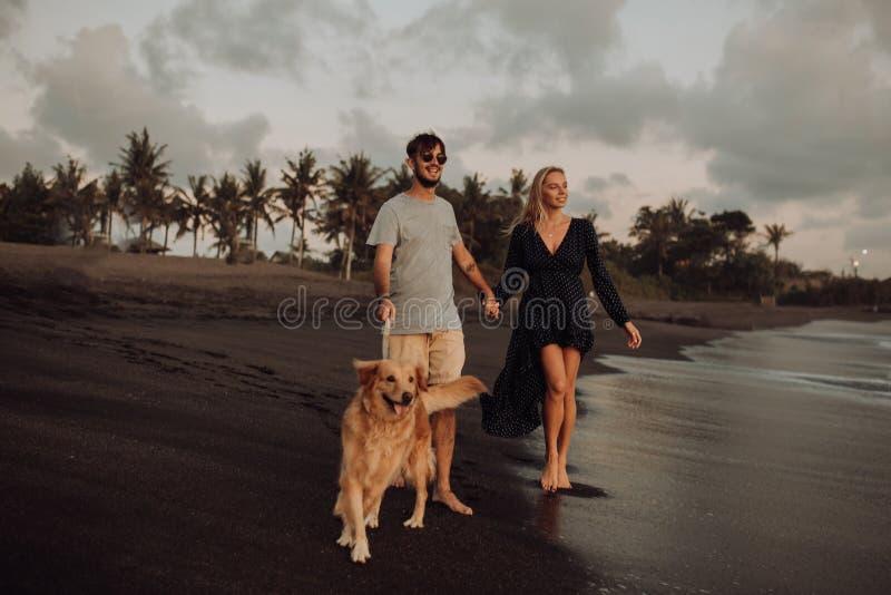 Pares jovenes del inconformista de la risa feliz hermosa con golden retriever en la playa océano una arena Ondas concepte de la l fotos de archivo