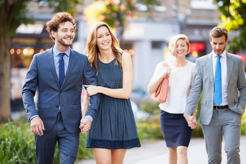 Pares jovenes del negocio que caminan a través de parque de la ciudad junto imagen de archivo