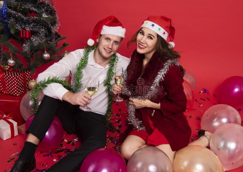 Pares jovenes del retrato que sostienen los vidrios de champán y que sonríen mientras que celebra en fondo rojo La Navidad y Feli imagen de archivo libre de regalías