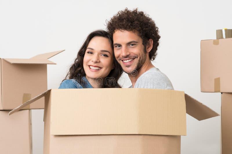 Pares jovenes dentro de la caja de cartón fotografía de archivo libre de regalías