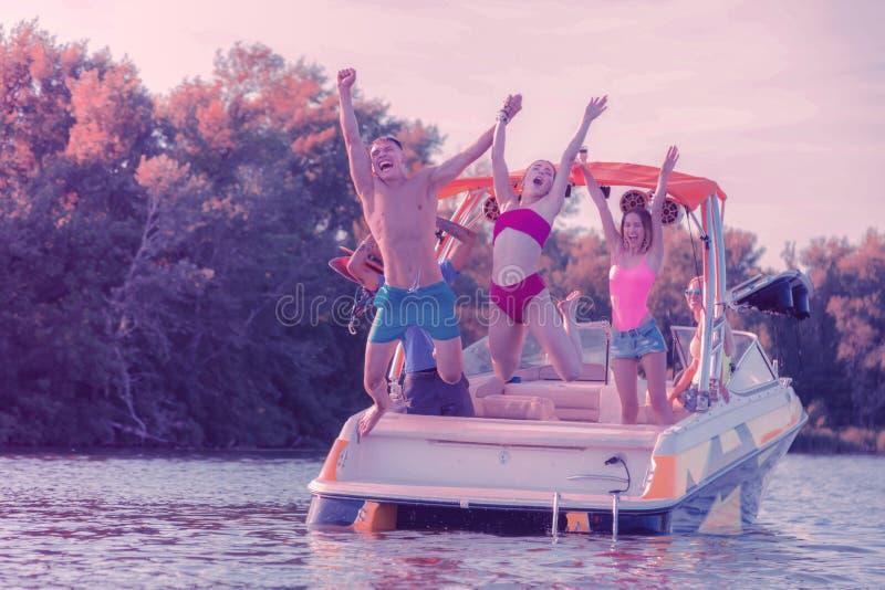 Pares jovenes deportivos alegres que saltan en el río fotos de archivo libres de regalías