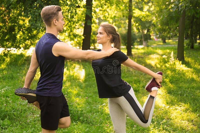 Pares jovenes deportivos que entrenan al aire libre fotografía de archivo