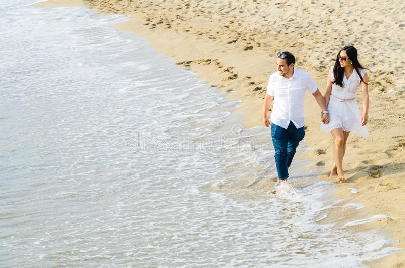 Pares jovenes descalzos que caminan de común acuerdo a lo largo de una playa en el borde de la resaca foto de archivo