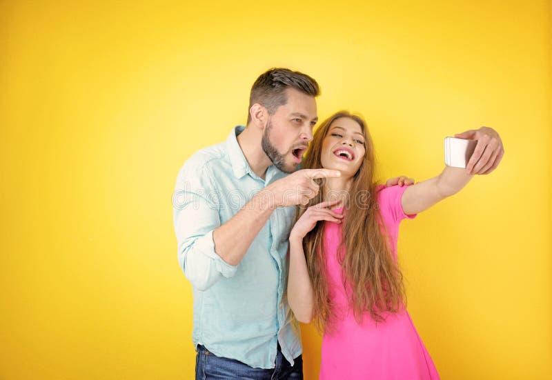 Pares jovenes divertidos que toman el selfie en fondo fotos de archivo libres de regalías