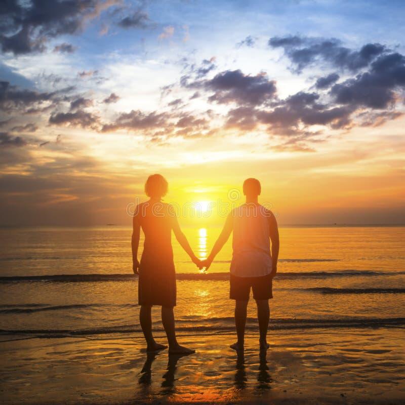 Pares jovenes durante luna de miel en una playa tropical, colocándose en el resplandor de una puesta del sol asombrosa Amor imagenes de archivo