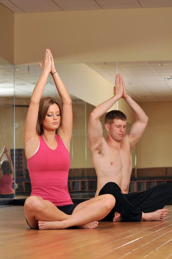 Pares jovenes durante una sesión de la yoga foto de archivo