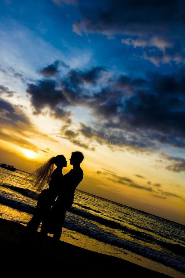 Pares jovenes el día de boda en la playa tropical y la puesta del sol foto de archivo