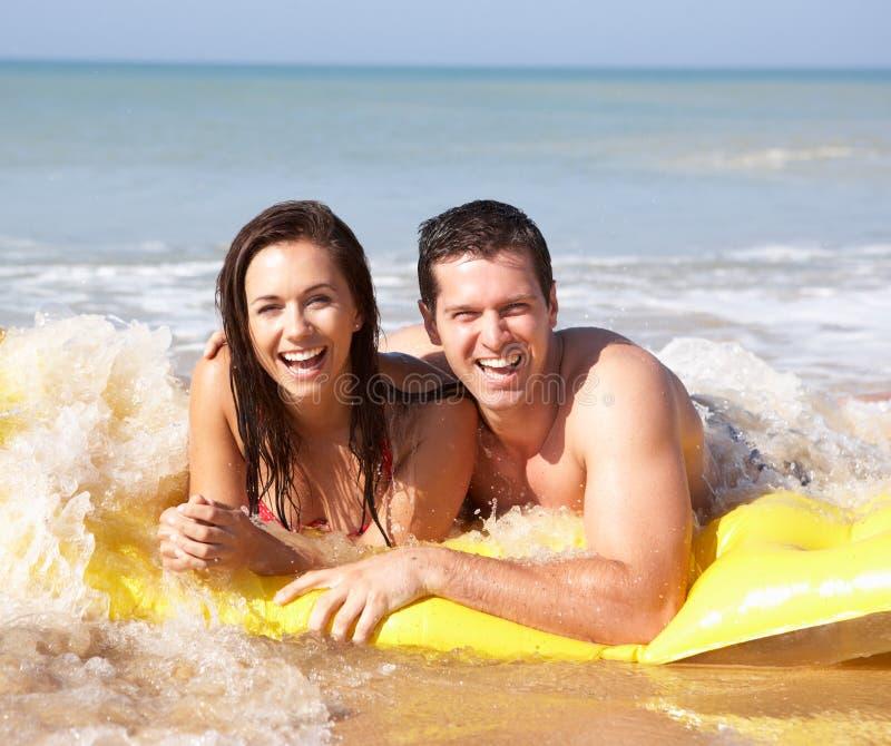 Pares jovenes el día de fiesta de la playa imágenes de archivo libres de regalías