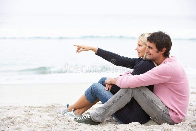 Pares jovenes el el día de fiesta que se sienta en la playa del invierno imagenes de archivo
