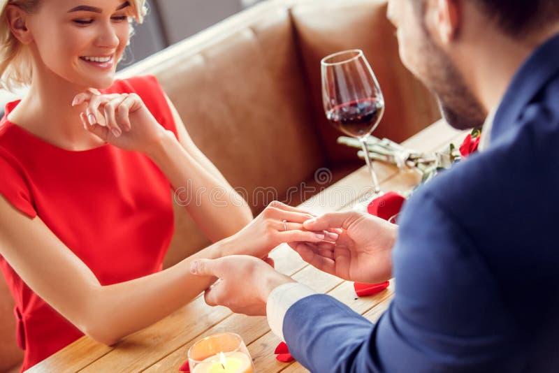 Pares jovenes el fecha en el anillo de la oferta de la mujer del restaurante que lleva que se sienta feliz imagenes de archivo