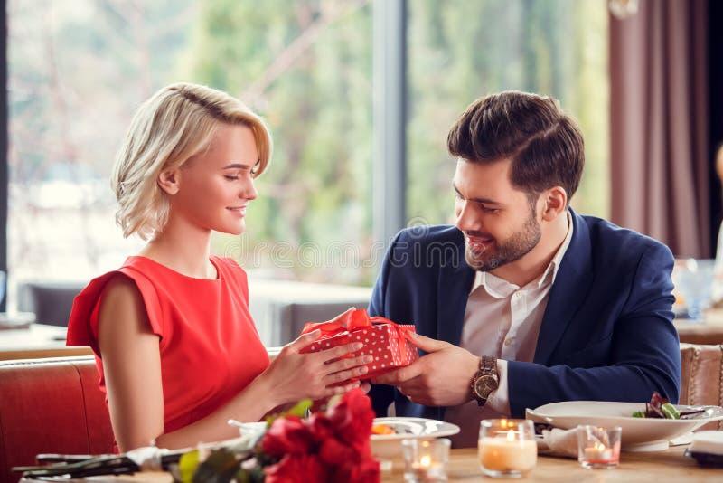 Pares jovenes el fecha en el hombre que se sienta del restaurante que da la caja de regalo a la sonrisa de la mujer feliz imagenes de archivo