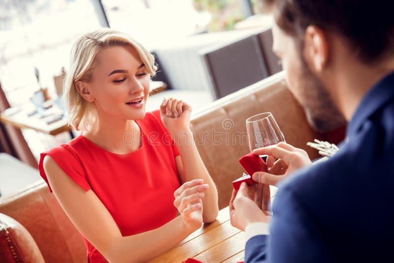 Pares jovenes el fecha en hombre que se sienta del restaurante proponer con la mujer del anillo que parece sorprendida imágenes de archivo libres de regalías