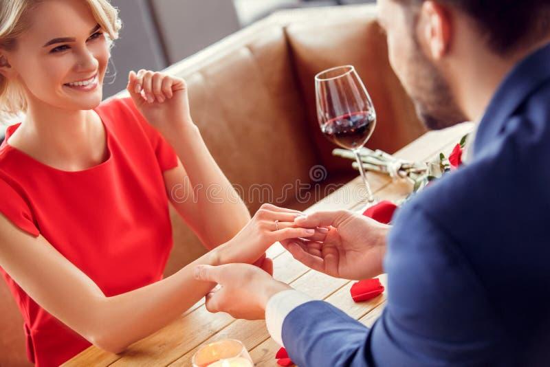 Pares jovenes el fecha en la mano de la tenencia del hombre del restaurante que se sienta del anillo de la oferta de la mujer que imagen de archivo