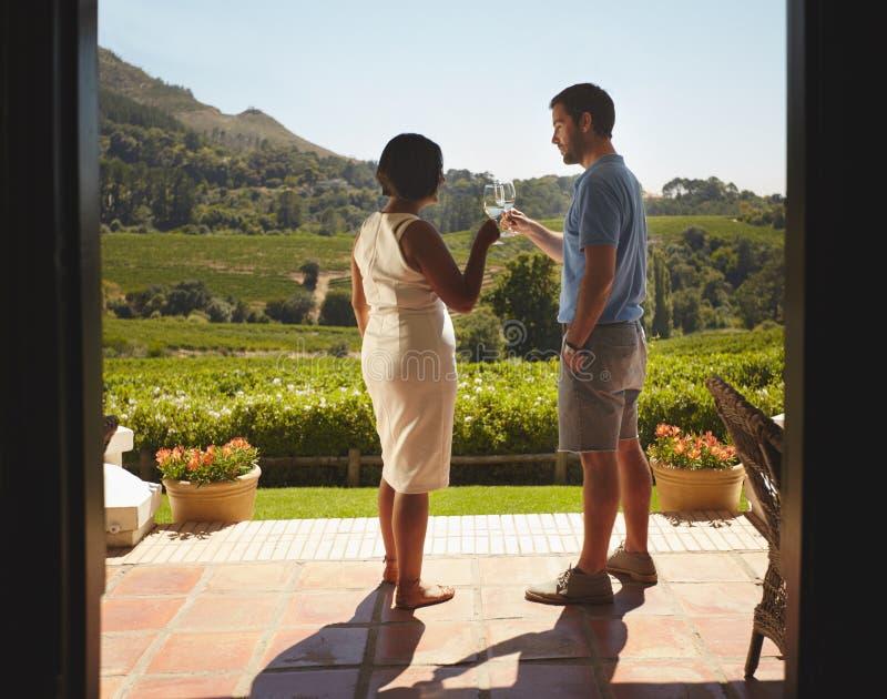 Pares jovenes el las vacaciones que celebran con el vino fotos de archivo libres de regalías