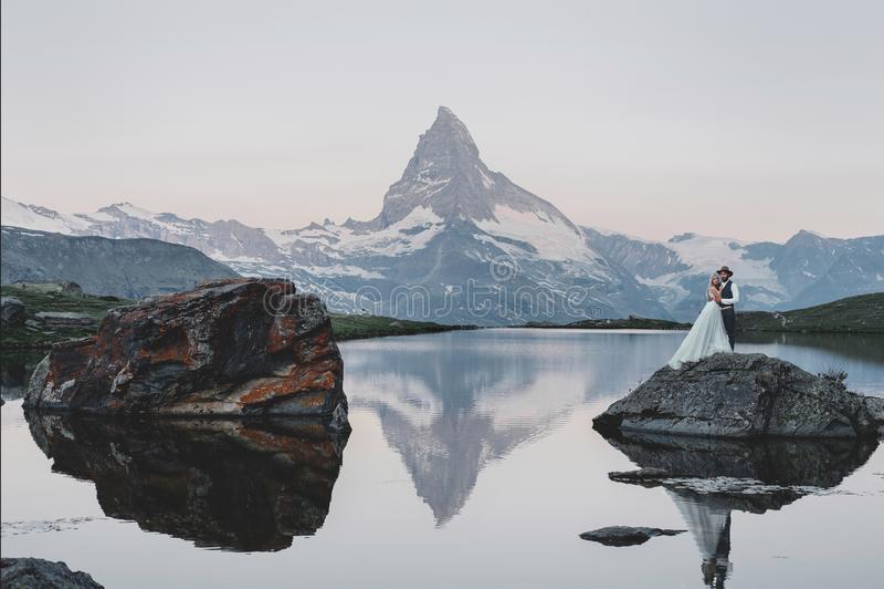 Pares jovenes elegantes de la boda que presentan en el moun hermoso de Cervino fotografía de archivo libre de regalías
