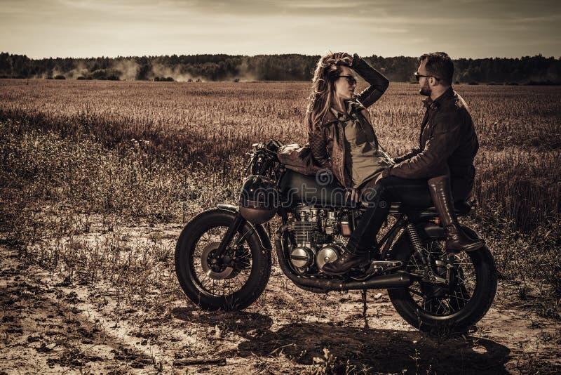 Pares jovenes, elegantes del corredor del café en las motocicletas de encargo del vintage en campo fotografía de archivo