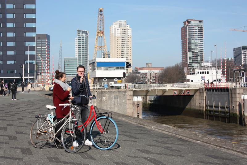 Pares jovenes en amor con los turistas que viajan en Rotterdam con sus bicicletas en un día del otoño visitando el puerto y el  imágenes de archivo libres de regalías