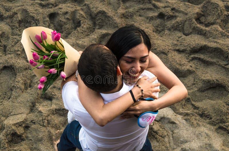 Pares jovenes en amor, con un ramo de tulipanes, abrazando imagen de archivo