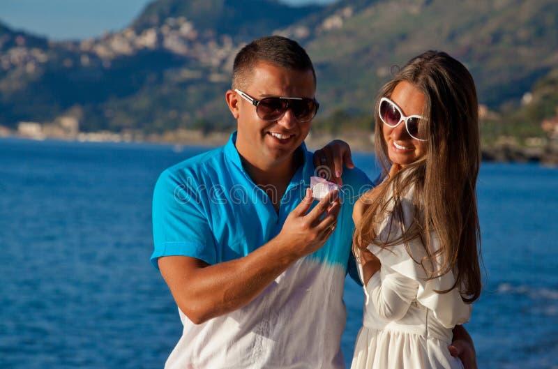 Pares jovenes en amor con una regalo-caja en la playa imagen de archivo