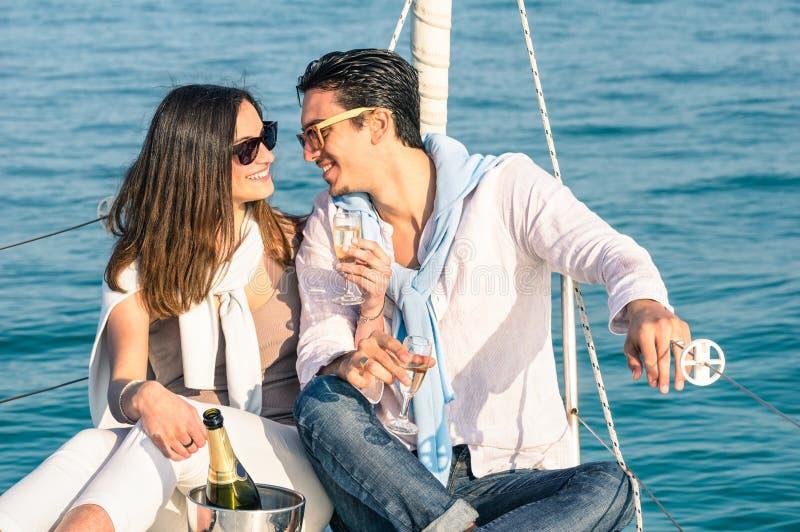 Pares jovenes en amor en el barco de vela con la flauta de champán foto de archivo libre de regalías