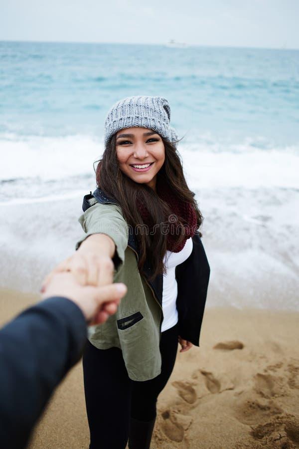 Pares jovenes en amor en el paseo romántico en la playa fotografía de archivo