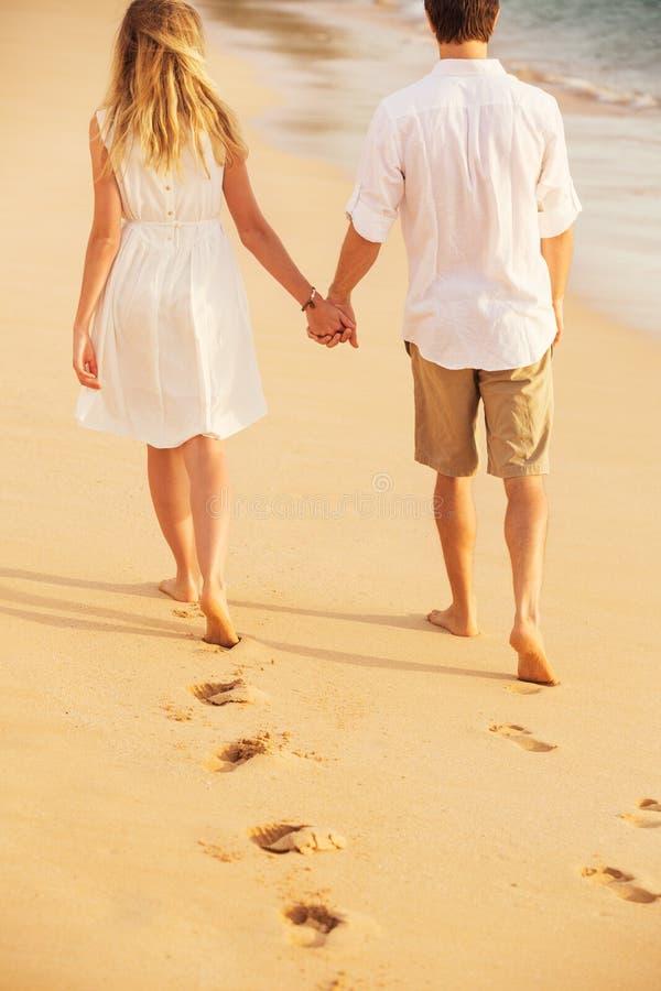 Pares jovenes en amor en la puesta del sol de la playa imagenes de archivo