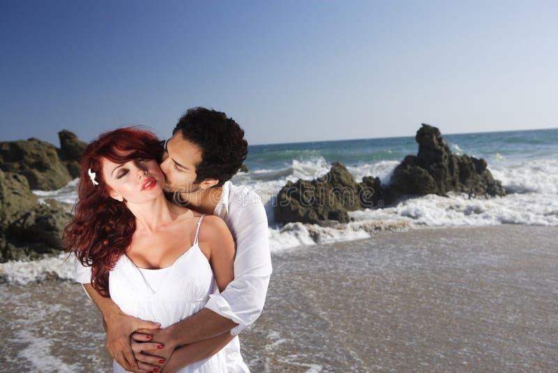Pares jovenes en besarse de la playa foto de archivo