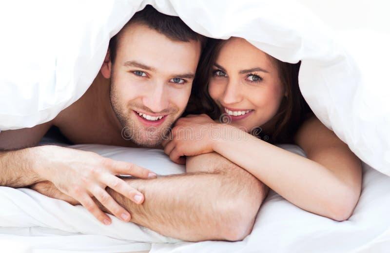 Pares jovenes en cama imagen de archivo libre de regalías