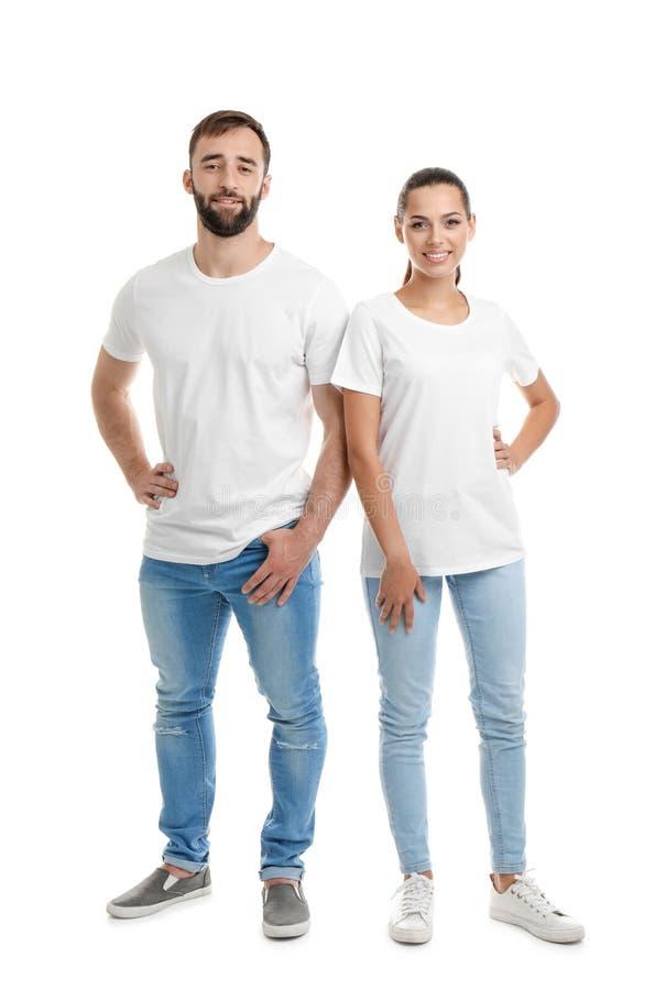 Pares jovenes en camisetas en el fondo blanco fotografía de archivo libre de regalías
