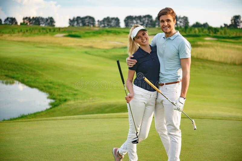 Pares jovenes en campo de golf fotografía de archivo